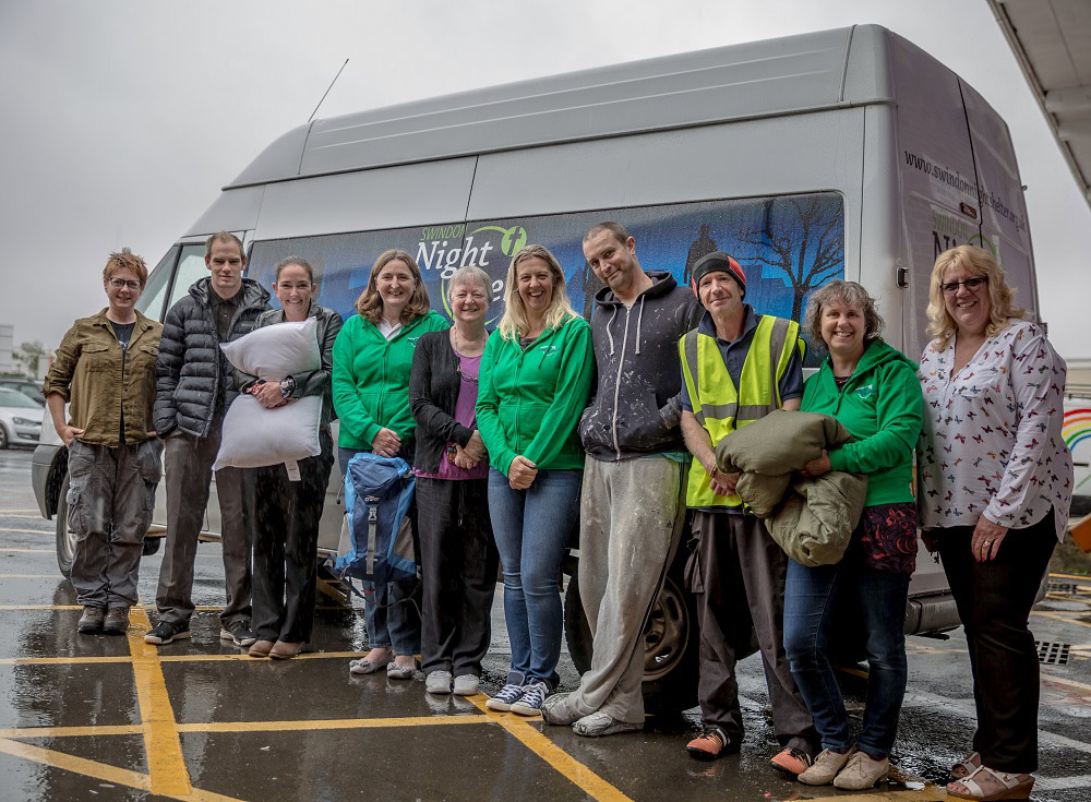 Staff and customers standing in a line in front of a night shelter van