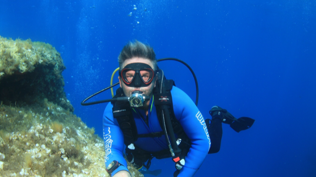 Man scuba diving, looking at the camera
