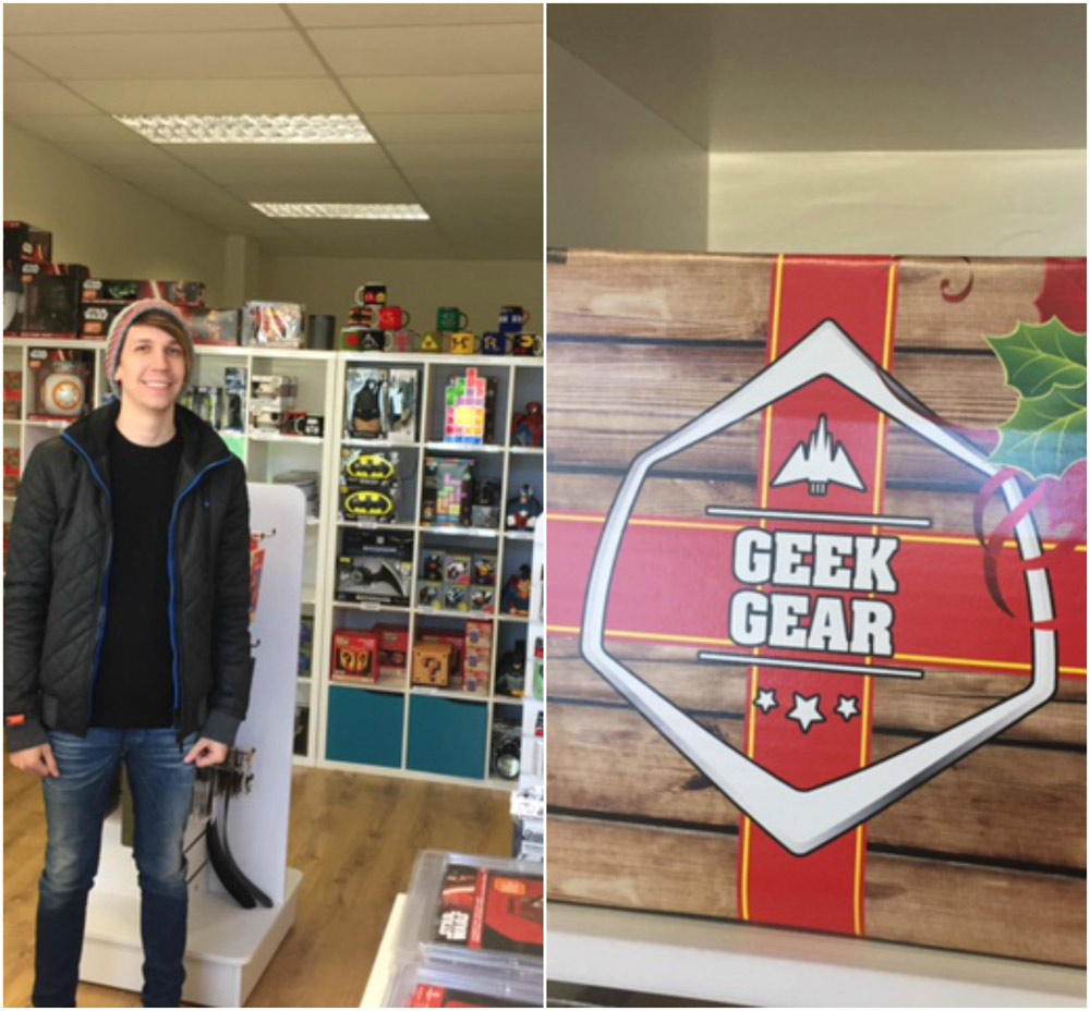 Young man wearing a beanie hat and jeans in front of merchandise and the Geek Gear logo