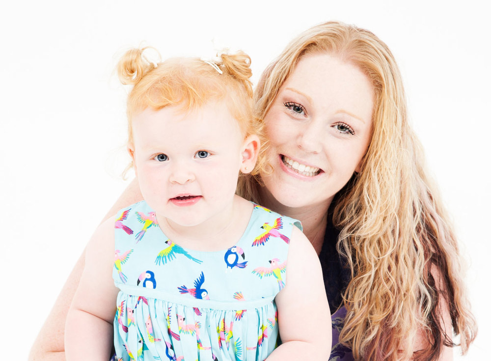 Young woman with long blonde hair hugging a toddler